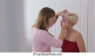 Professional make-up artist plucking eyebrows of client in...