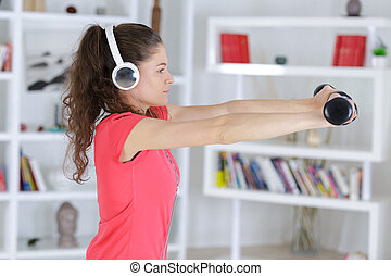 young fitness woman in gym and listen music with headset