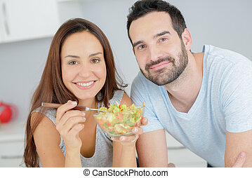 happy couple eating vegetable salad