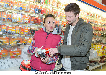 young entrepreneur buying spray lubricant in hardwarestore