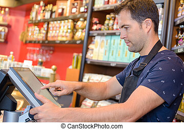 Man using touchscreen till