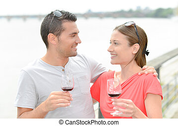 Couple enjoying wine by the river