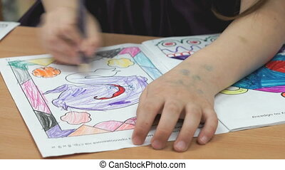 Child draws the pictures in the copybook using a color...
