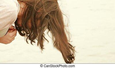 Brunette girl near river no face handheld shot. Long haired...