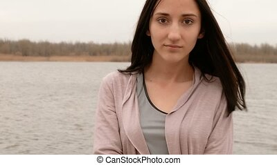 Young pretty girl was sad to stay on the river side, she was...