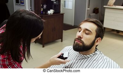 Barber woman trimming beard of client with clipper at...
