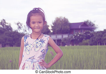 asian children girl in green rice filed