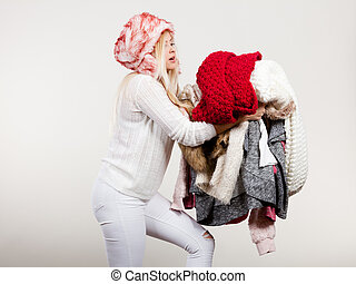 Woman in furry hat holding clothes pile - Woman in furry hat...