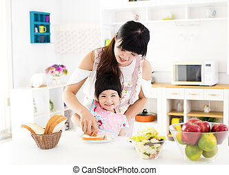 little girl helping her mother prepare food in the kitchen