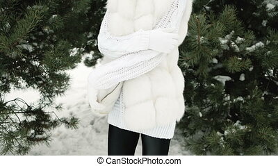 Beautiful young woman posing in a snowy pine tree in a white...