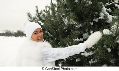 Beautiful woman in white dress runs and rejoices in the winter.