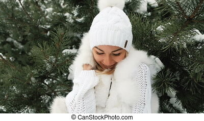 Young woman in white dress freezes under spruce and smiling.