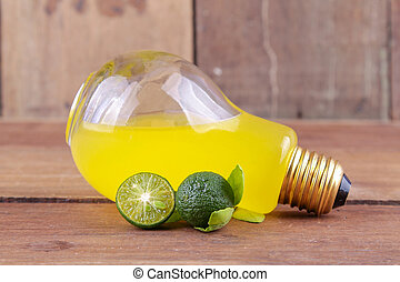 calamansi on bulb with orange drink on wood background