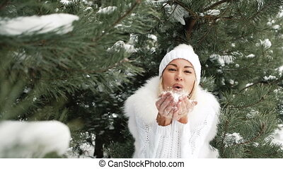 Laughing woman in the white dress blowing on the snow on her hands
