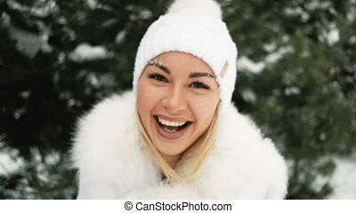 Happy woman in a white hat and furry mittens in green pines....