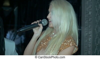 Beautiful young blond woman sings a song. Slow motion