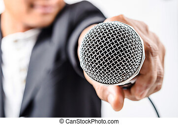 Businessman making speech with microphone and hand...