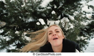 Blonde woman in a snow tree rejoices revolves around and sends kisses