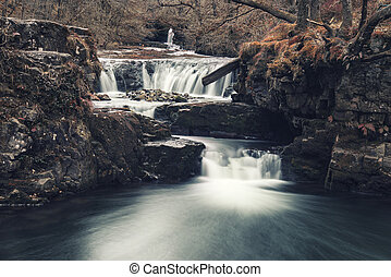 Beautiful waterfall landscape image in forest during Autumn Fall in Wales UK