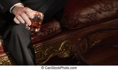 businessman drinking brandy and puts the glass on the coffee...