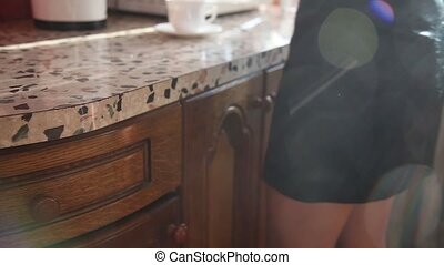 Young woman in a short black skirt, pouring tea in kitchen...