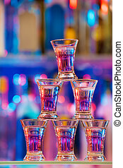 Pyramid of six shot glasses with cocktails