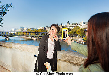 Woman taking a photograph of her friend in Paris