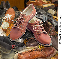 New mens shoes on pile of old different worn footwear - Pair...