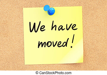 We Have Moved! Text on a sticky note pinned to a corkboard....