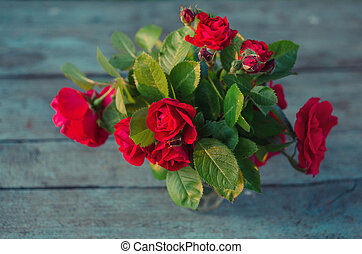 Beautiful red roses on grunge wooden table