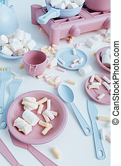 Colorful plastic tableware and marshmallows on the table