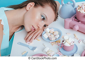 Tired woman lying on table with plasic tableware and...