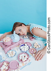 Exhausted woman lying on table with plasic dishes and...