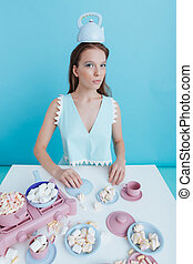 Woman with teapot on head playing using marshmallows and...