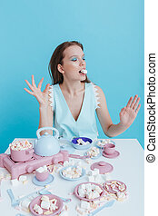 Playful young woman playing with plastic tableware and...