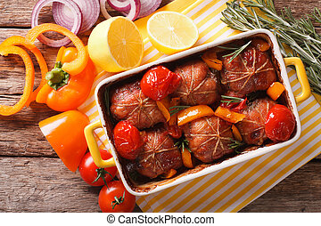 Roll of rabbit baked with tomato and pepper in baking dish....