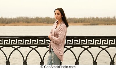 Young woman in the casual wear is standing in front of metal fence of embankment in the middle of a frame. Autumn trees on far riverbank