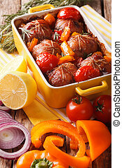 Baked rolls of rabbit with vegetables close up in baking...
