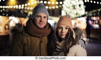 happy couple hugging at christmas market - love, winter...