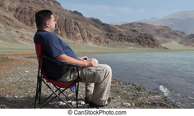 Man relaxing at mountain lake