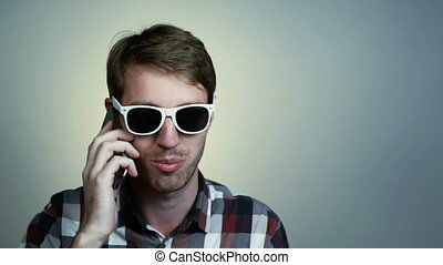 Young man in glasses talking on cell phone - Closeup...