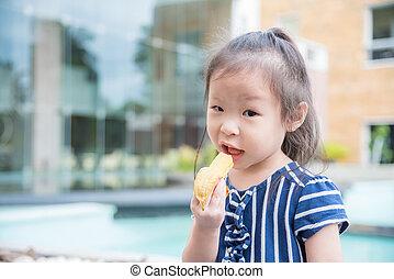 Little girl eating banana - Little asian girl eating banana...