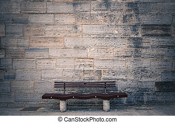 Wooden chair in front of  brick wall