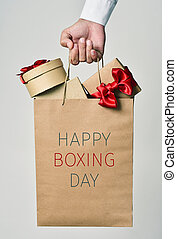 gifts and text happy boxing day - closeup of the hand of a...