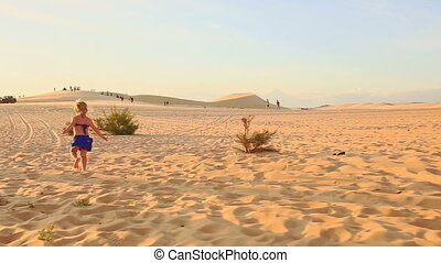 Backside Small Girl Runs Barefoot on Sand Dune to Hill at...