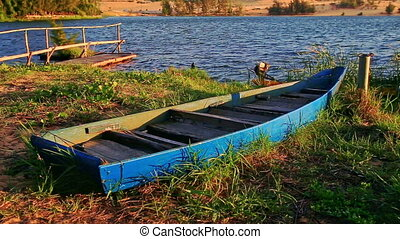 Empty Boat Bound on Grass Bank at Wooden Pier by Lake -...