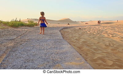 Small Girl Runs Barefooted along Path by Sand Dunes at...