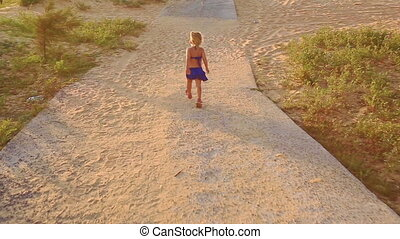Small Girl Runs along Rocky Path by Grass Sand Dunes at...