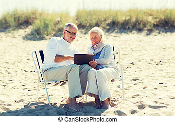 happy senior couple with tablet pc on summer beach - family,...