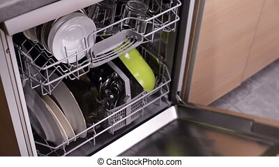 Woman opening dishwasher, closeup video